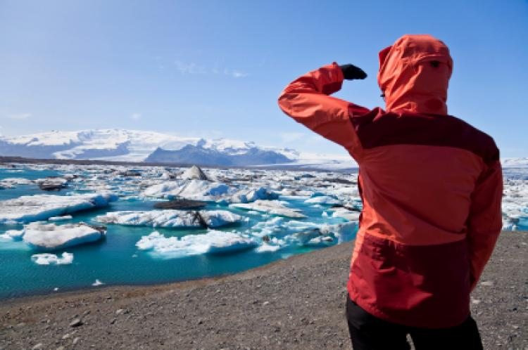 Female hiker looking across the Iceberg Lagoon, Jokulsarlon, Iceland filled with glacial Icebergs
