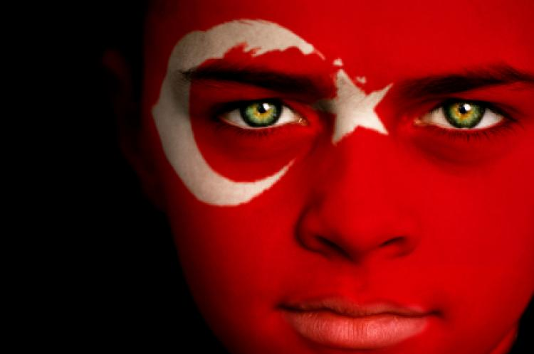 Image of young boy with Turkish flag painted on face and the inside of the Turkish Assembly building
