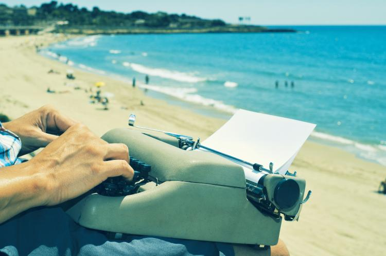 A young man typing on an old typewriter at the beach.