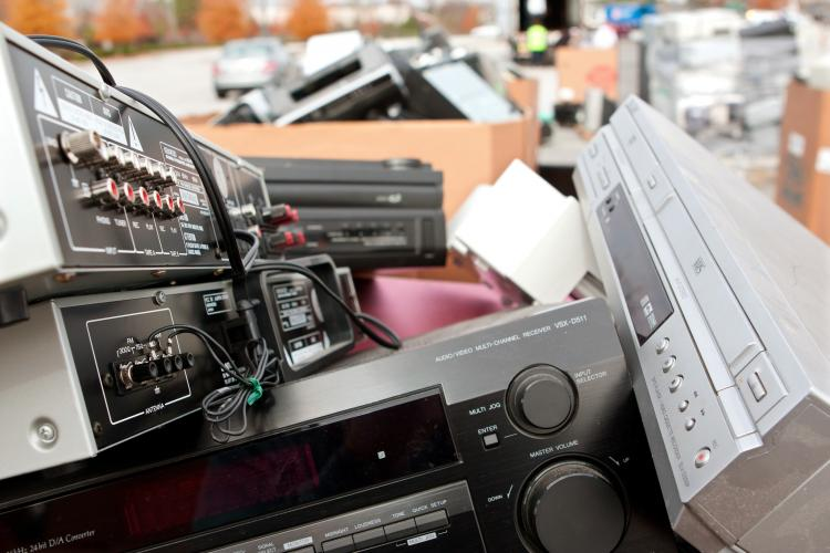 Old stereos and electronics pile up at a recycling event.