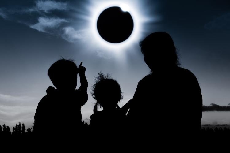 Silhouettes of two children and a woman watching the diamond ring effect on a totally eclipsed Sun.