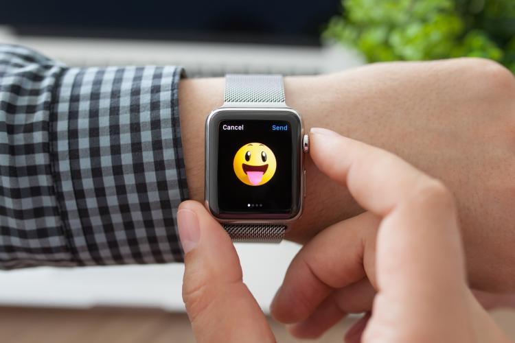 An Apple Watch with a smiley emoji on person's arm.
