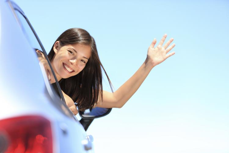 Woman waving hello out of a car window.