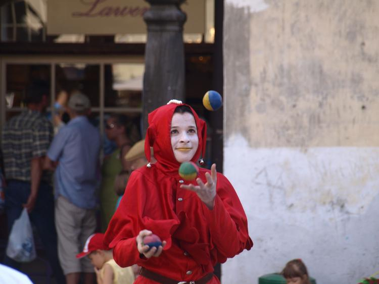 Young woman in clown costume juggling balls in an old market place on July 27, 2008, in Kazmierz Dolny, Poland.