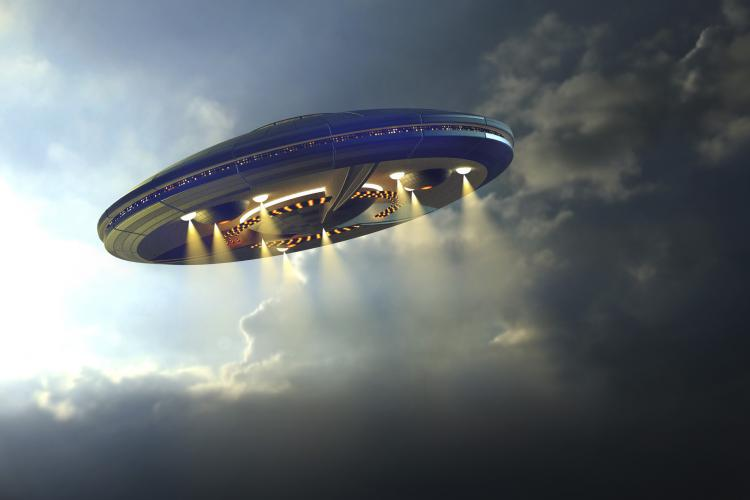 Artist rendition of alien UFO saucer flying above Earth with a background of clouds.