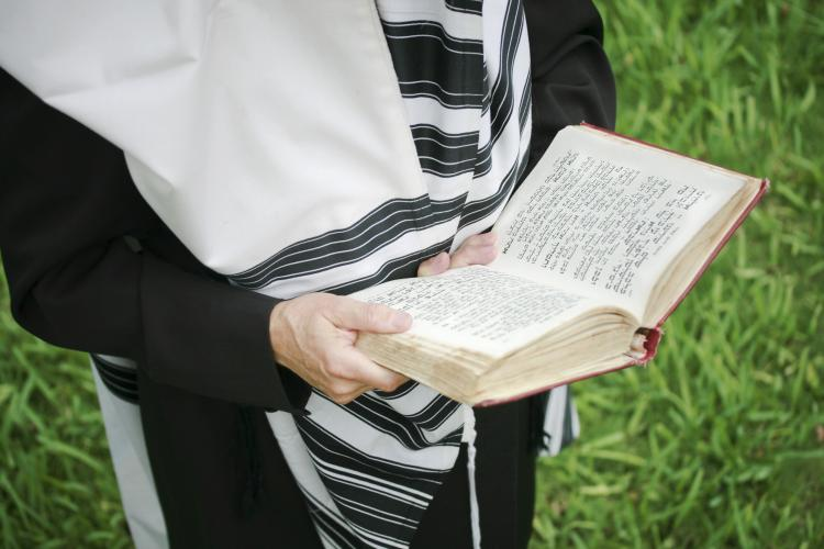 A Jewish man praying with a tallis (prayer shawl).