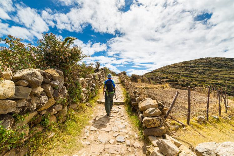 Female backpacker walking on ancient Peruvian trail.