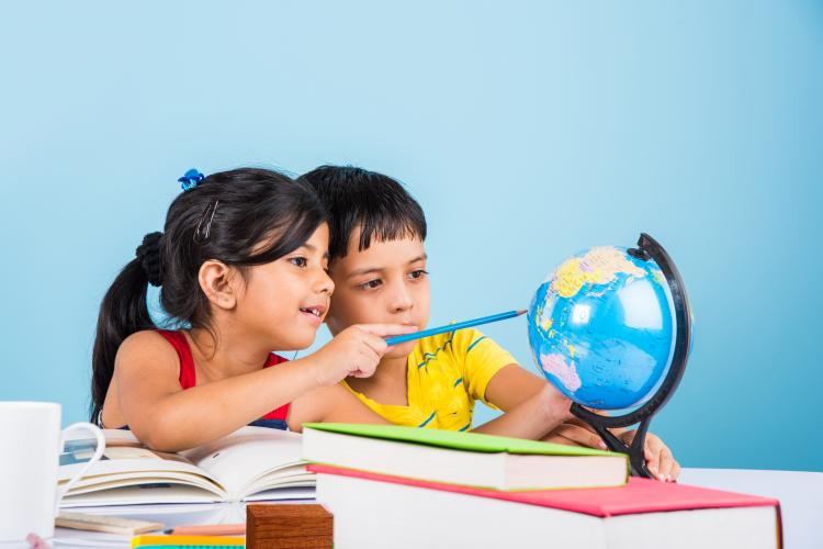 Young girl and boy studying a globe.