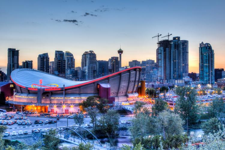 Sunset over the skyline of Calgary in Alberta, Canada with the Scotiabank Saddledome in the foreground.