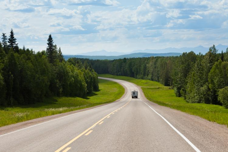 Recreational Vehicle on empty road of Alaska Highway Alcan in boreal forest taiga landscape south of Fort Nelson, British Columbia, Canada.