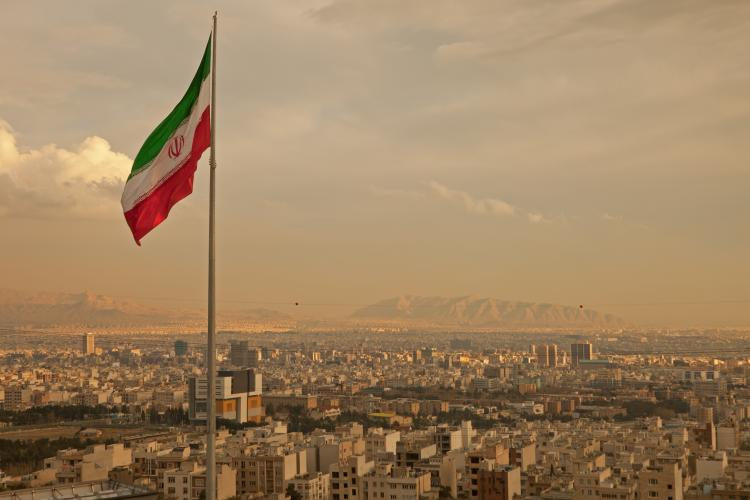 Iran flag waving in the wind above the skyline of Tehran lit by the orange glow of sunset.
