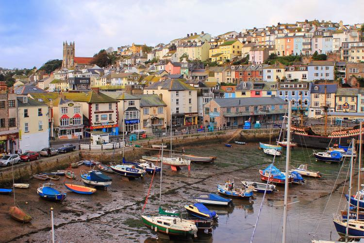 Small boats moored at low tide in the fishing port in Brixham, Devon, UK