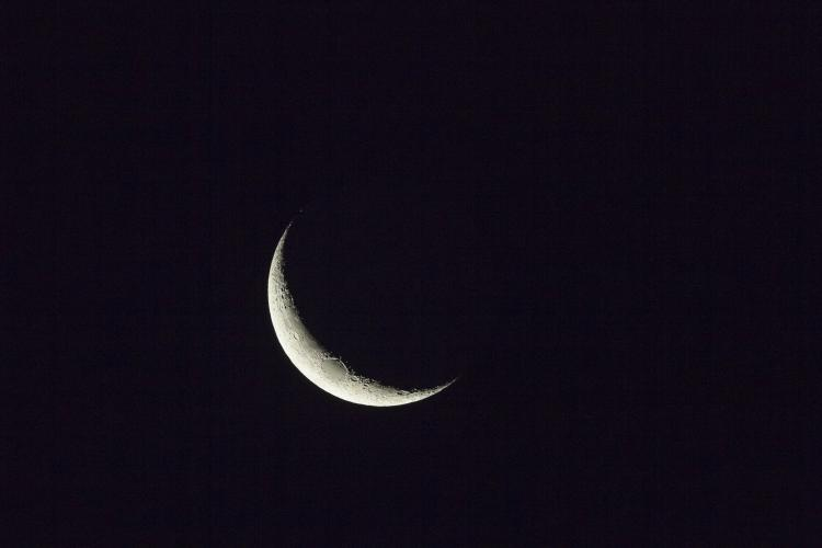 A Waining Crescent Moon against a black night sky illuminated from the left side.