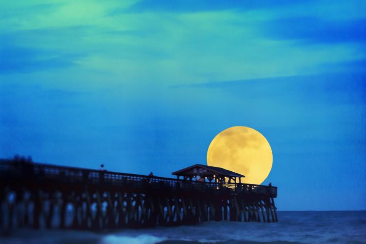 Full moon on the horizon at the end of a dock.