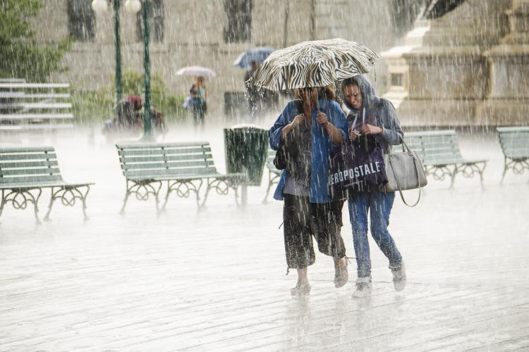 Two women walking under umbrella during heavy rain.