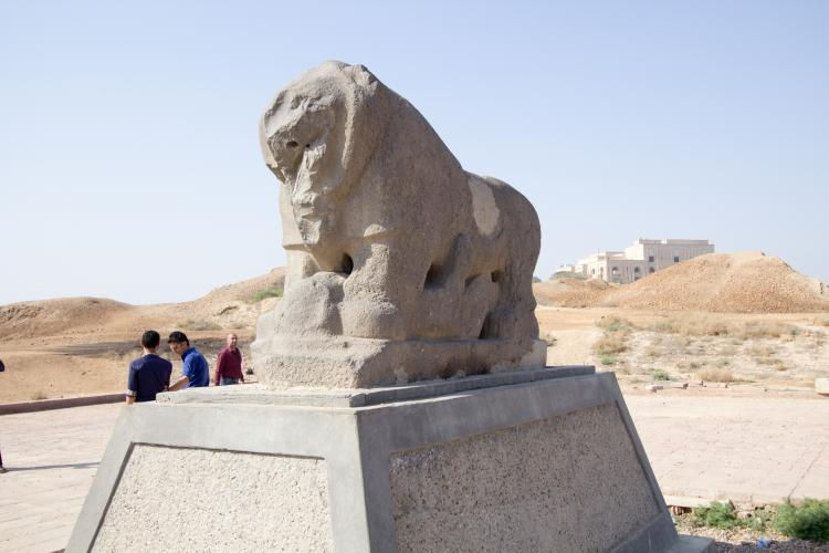 3 men next to the black basalt statue of the lion of Babylon which depicts a lion standing above a laying human in today's Iraq. March 20, 2015.
