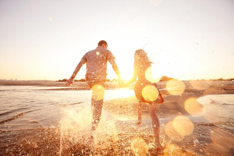 A happy couple running through the waves on a sunlit beach.