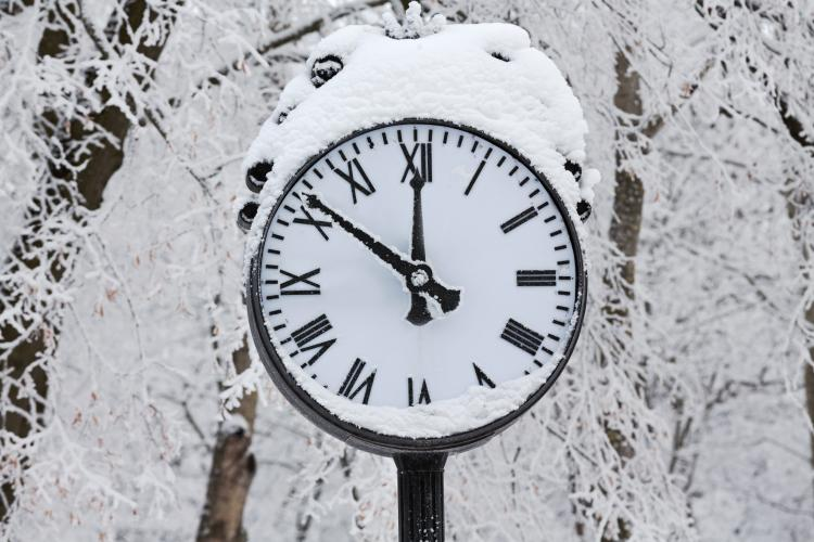 Clock with snow on it during the winter time.