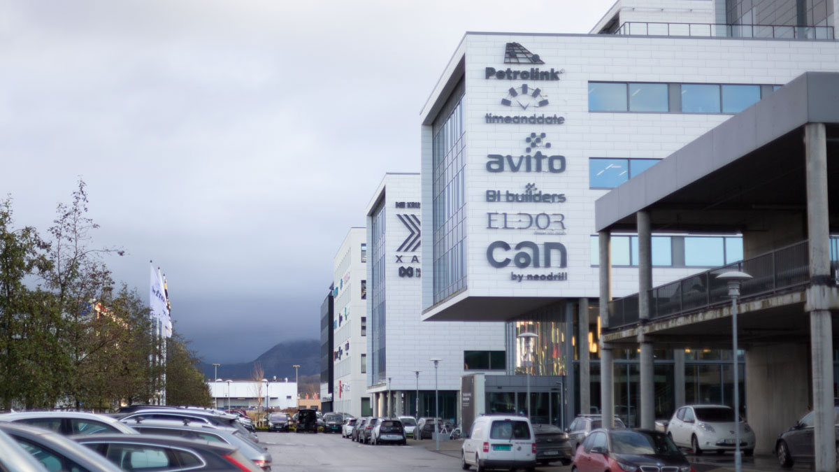 Photo of a grey office building with several company logos, including timeanddate.com. In the background are mountains and grey skies.