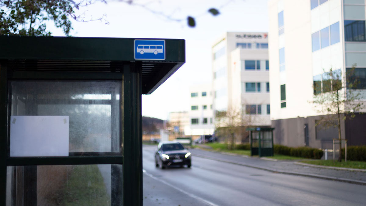 Bus stops on both sides of the road next to office buildings.