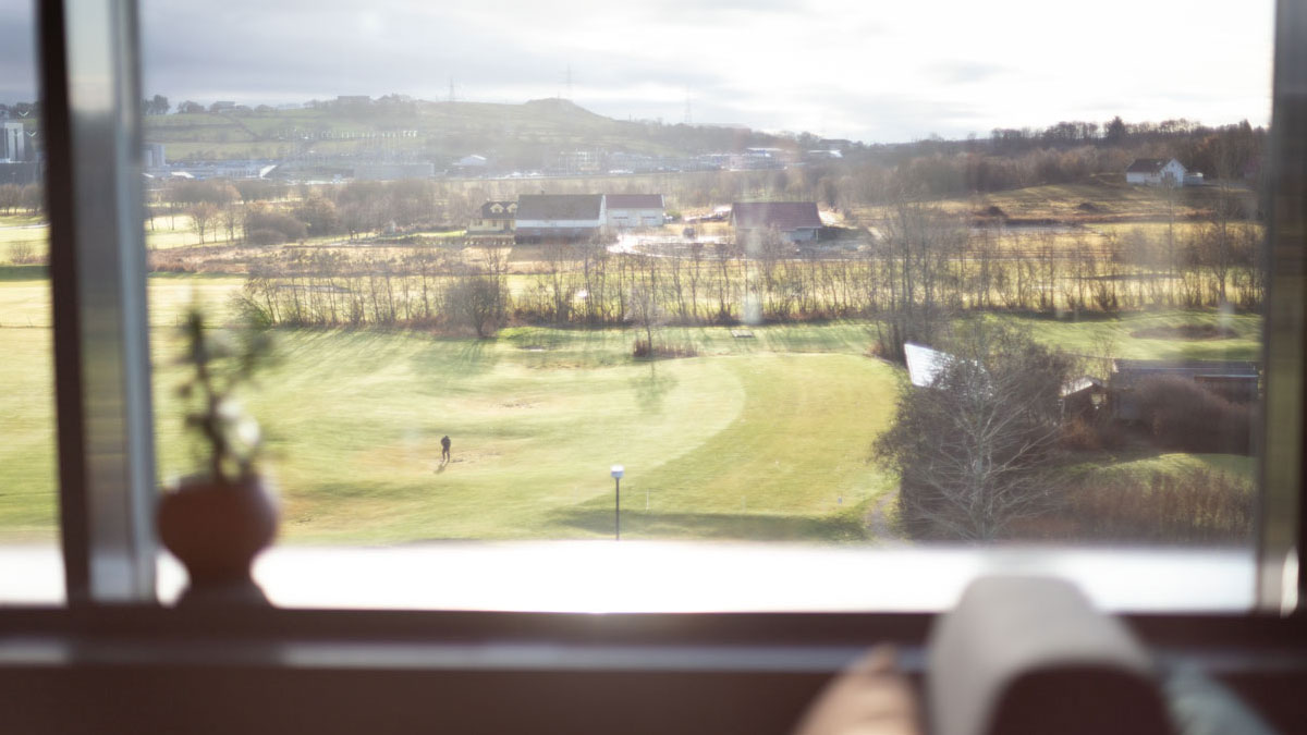 View of a golf course outside large windows.