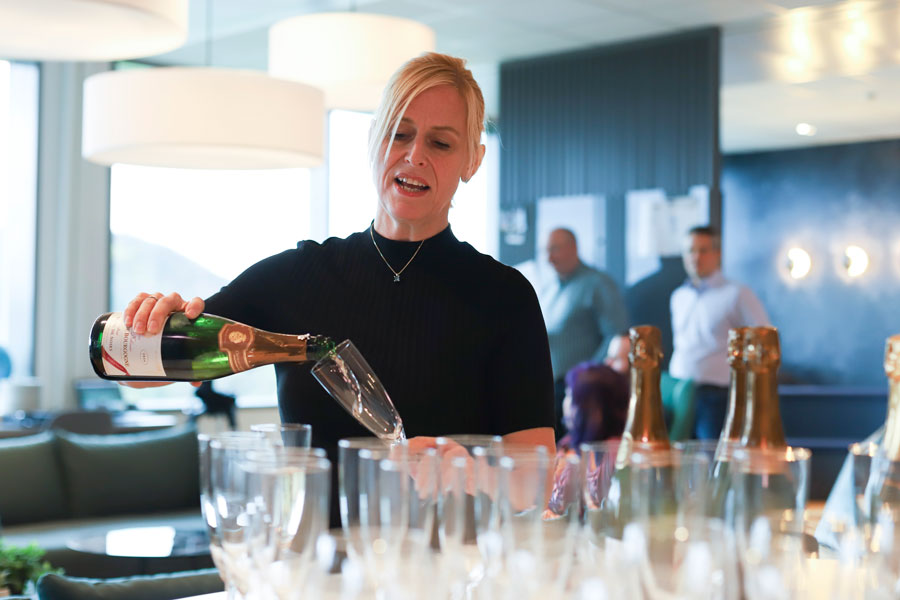 A blonde woman pouring sparkling wine