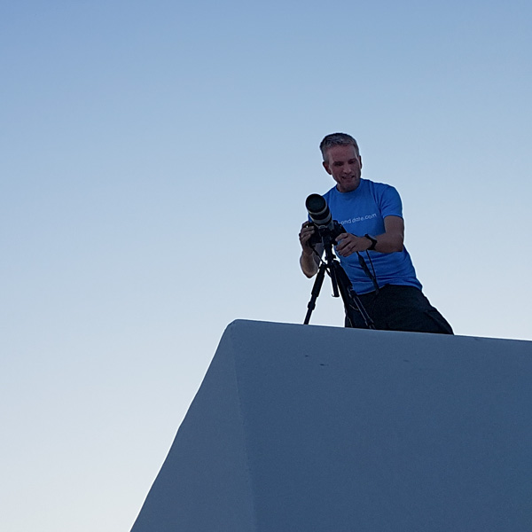 Picture of man on a roof with a camera.